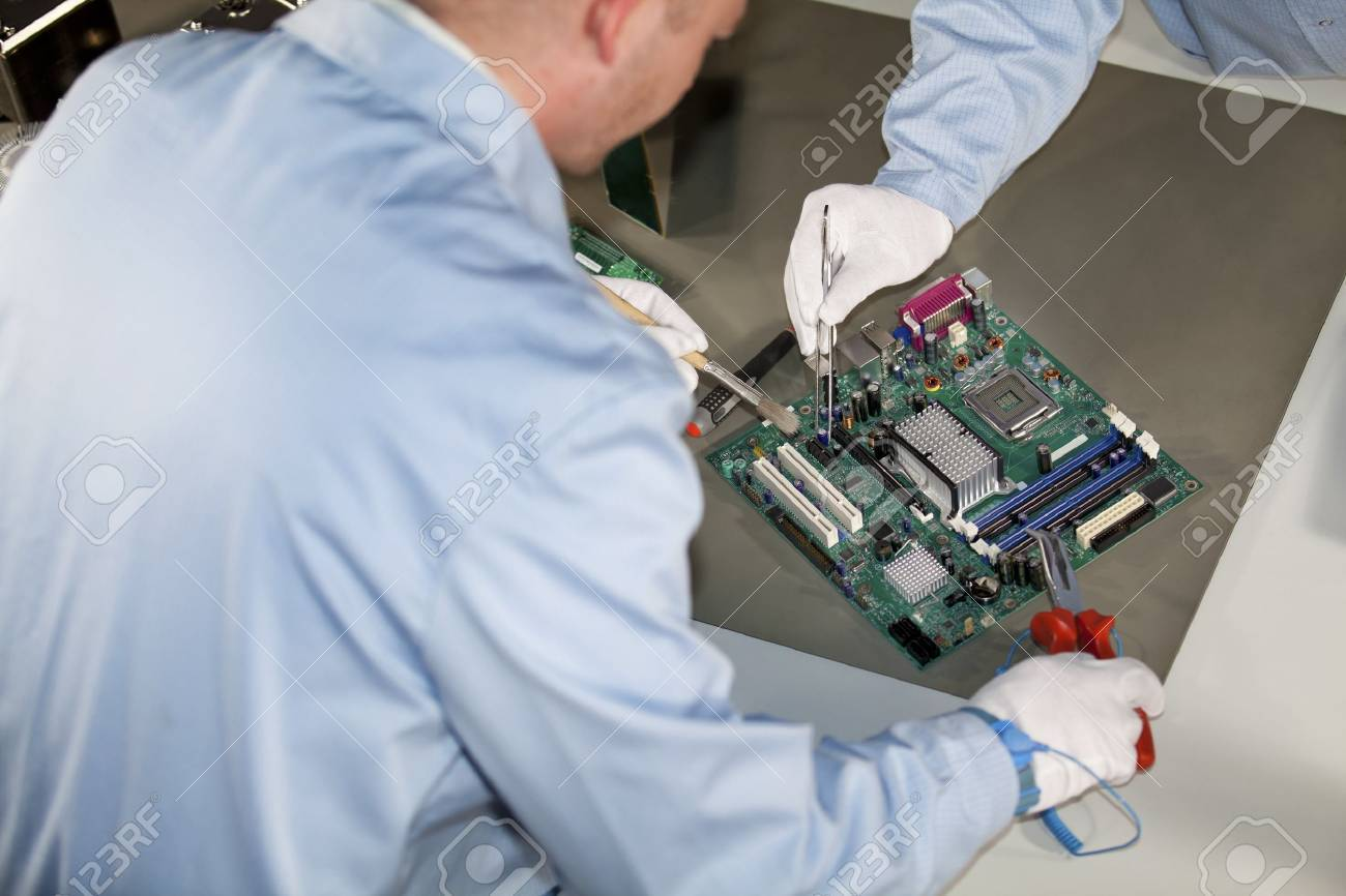 IT - engineers doing repairs and cleaning on a motherboard Stock Photo - 8860393