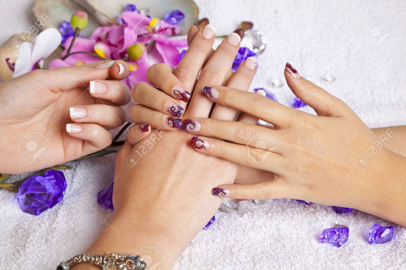 A beauty concept - hands with acrylic fingernails, flowers, shells and crystals Stock Photo - 12136370
