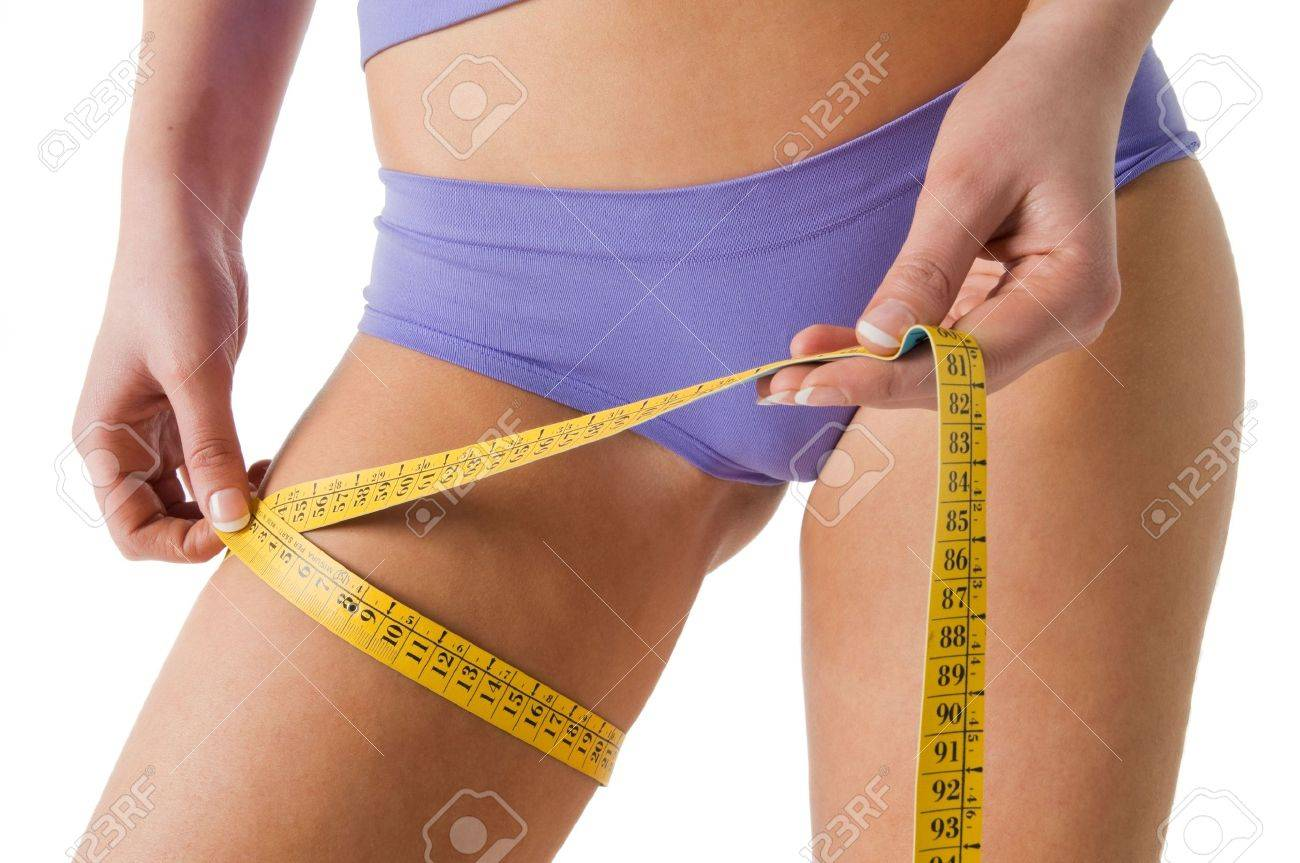 Girl measuring her thigh checking the result of diet. Stock Photo - 3001188