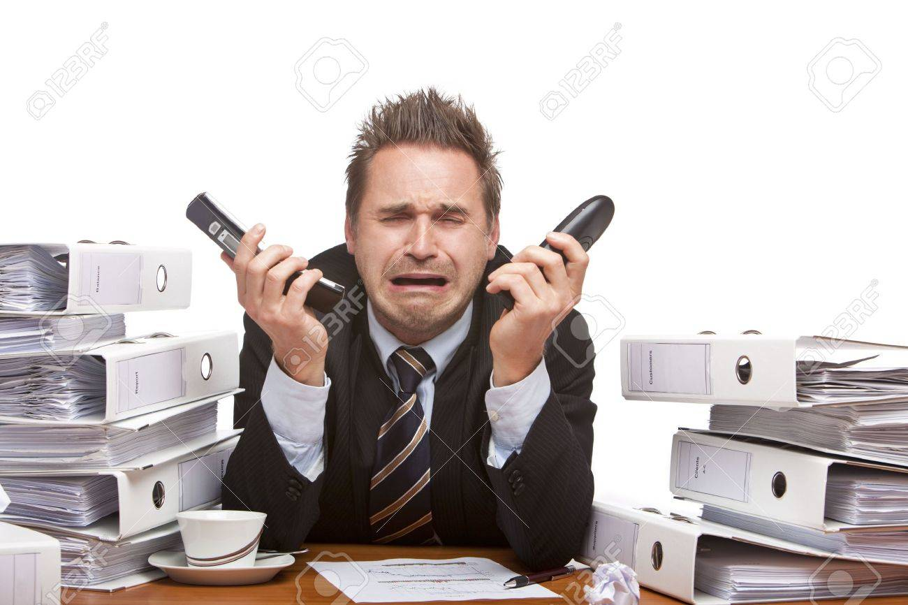 Frustrated office worker on the phone holding stock photo image - Frustrated Phone Young Businessman Is Sitting On Desk Holding Two Telephones And Crying Because