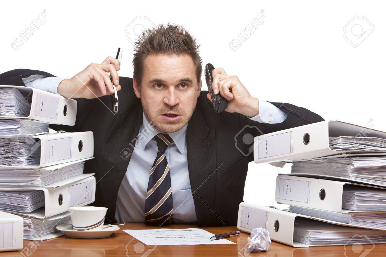 Young businessman is sitting on desk betweent folder stacks and having two telephones on his ears.  Isolated on white. Stock Photo - 6440139