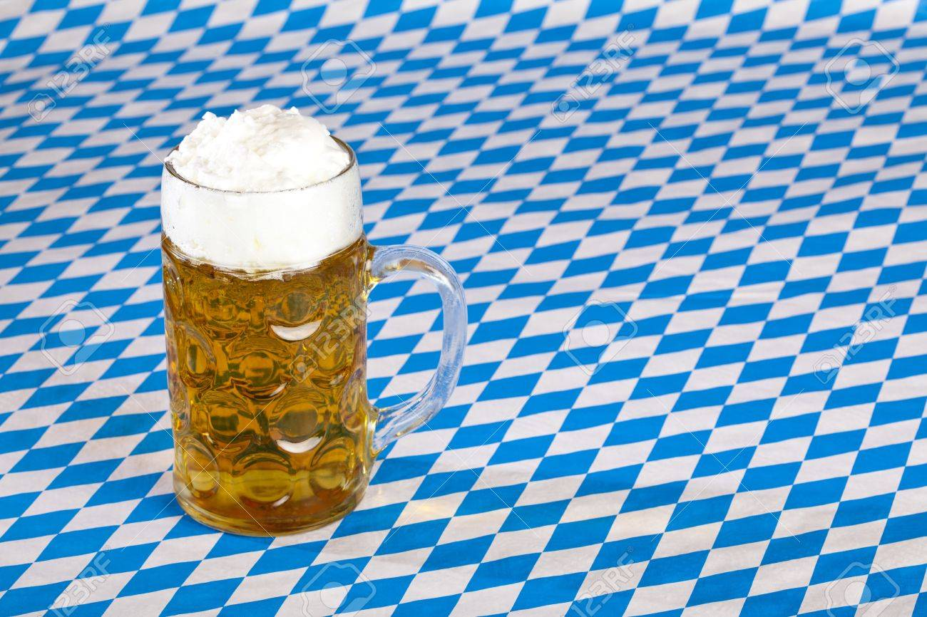 Oktoberfest beer stein  and Bavarian flag in background. Stock Photo - 7706870