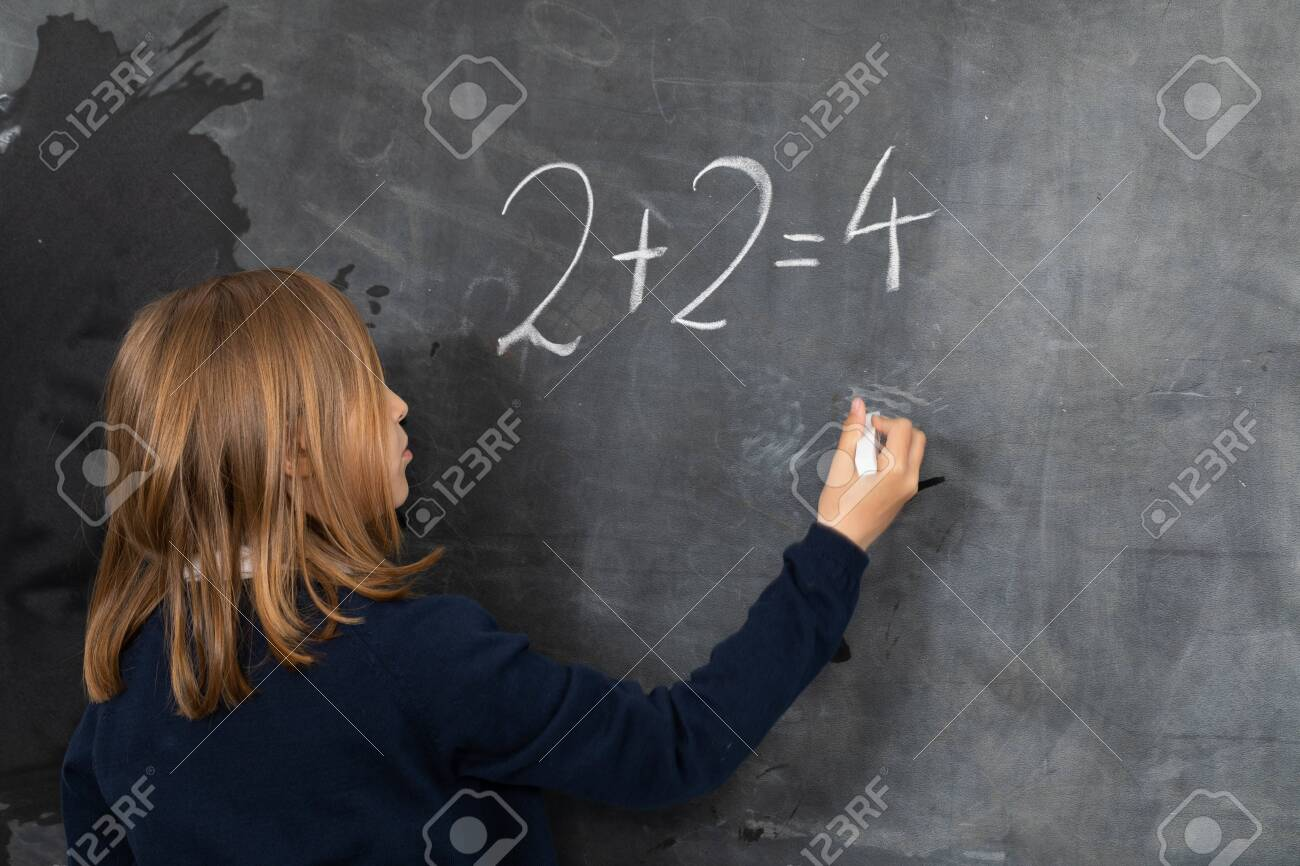 He writes on the chalkboard with chalk. Math problem. A girl at the chalkboard. - 148091461