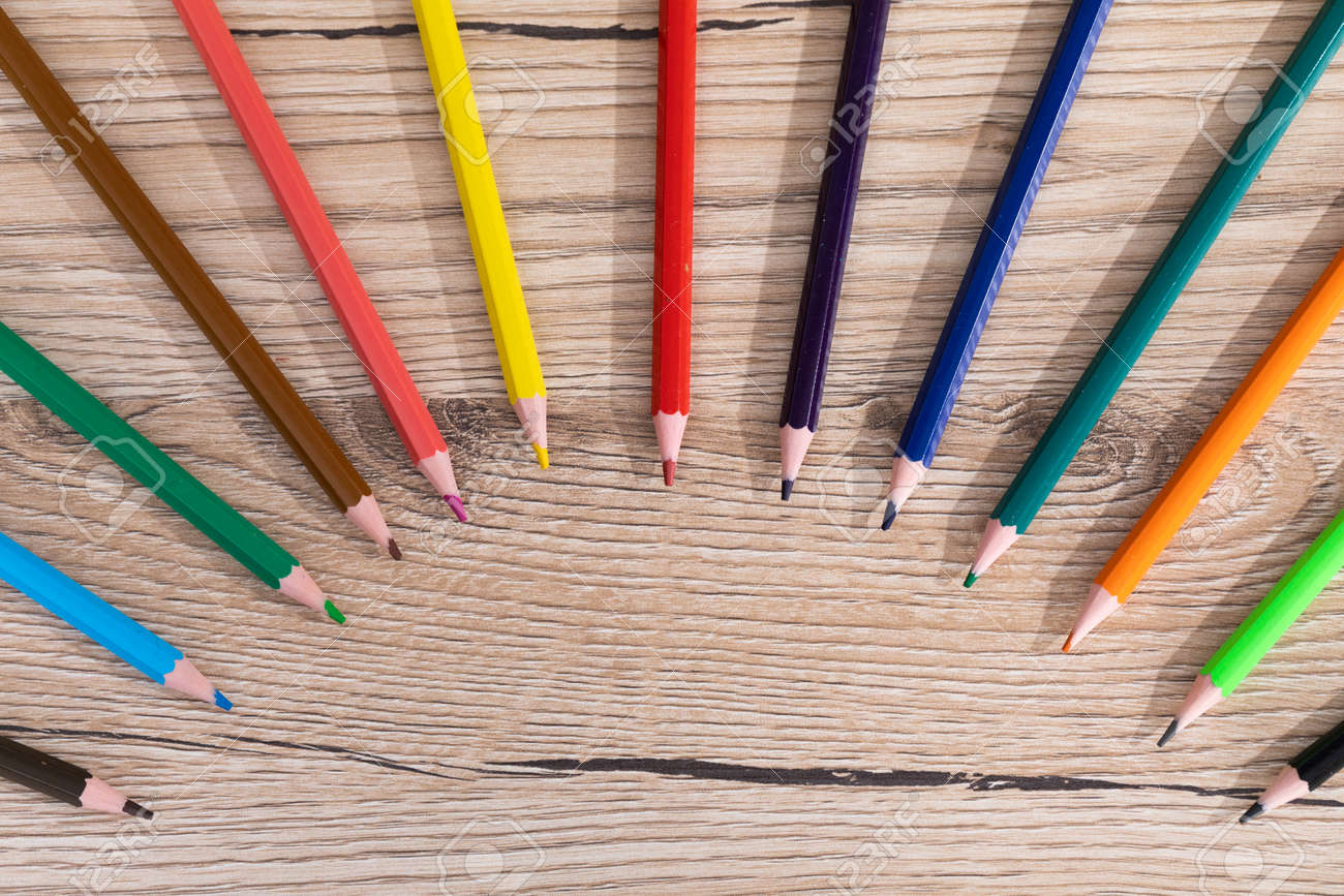 New unused colored pencils. Each of them is sharp and accurate. Wooden desk top. - 148247346