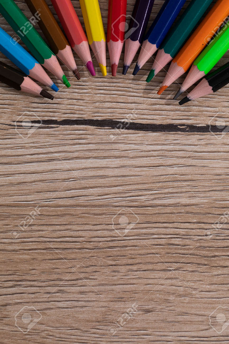 New unused colored pencils. Each of them is sharp and accurate. Wooden desk top. - 148247349
