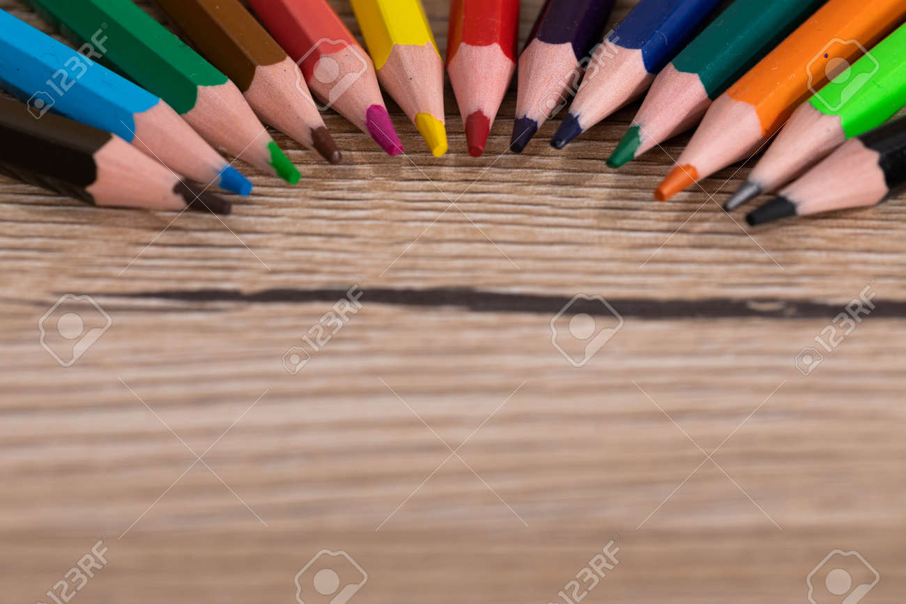 New unused colored pencils. Each of them is sharp and accurate. Wooden desk top. - 148247353