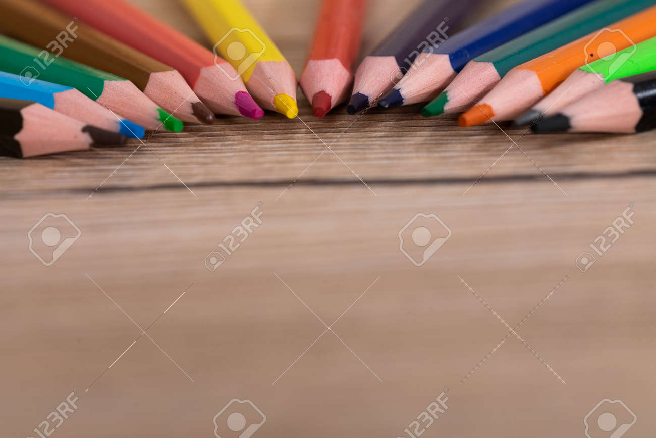 New unused colored pencils. Each of them is sharp and accurate. Wooden desk top. - 148247354