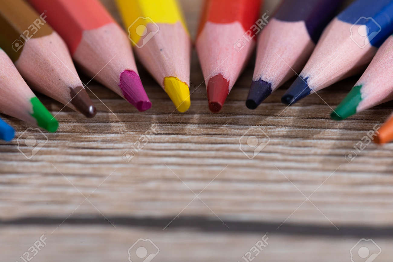 New unused colored pencils. Each of them is sharp and accurate. Wooden desk top. - 148247355
