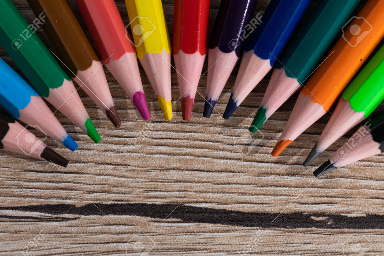 New unused colored pencils. Each of them is sharp and accurate. Wooden desk top. - 148247357