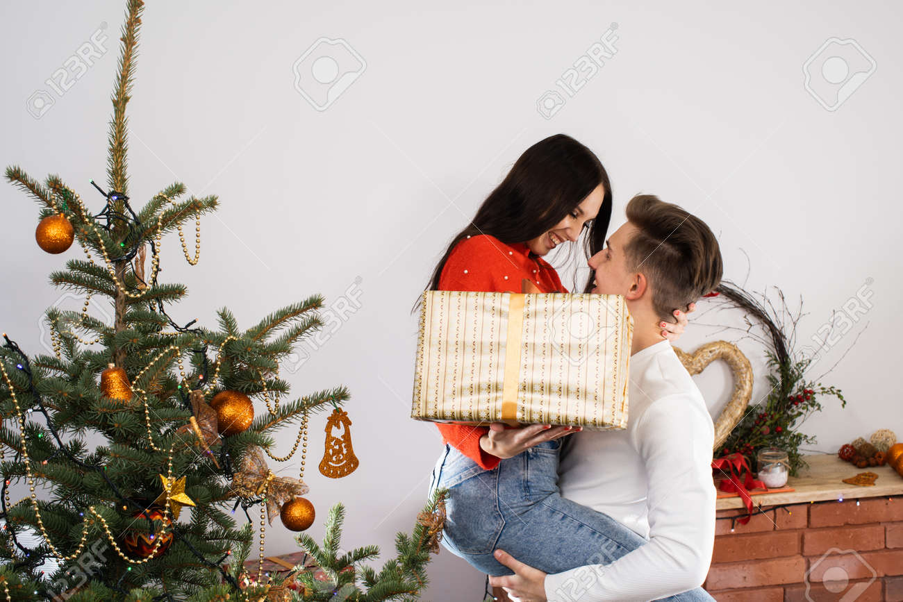 The fiance lifted his partner up in a fit of joy. Lovers flirt in a decorated living room at home. December Christian holidays. - 161324274