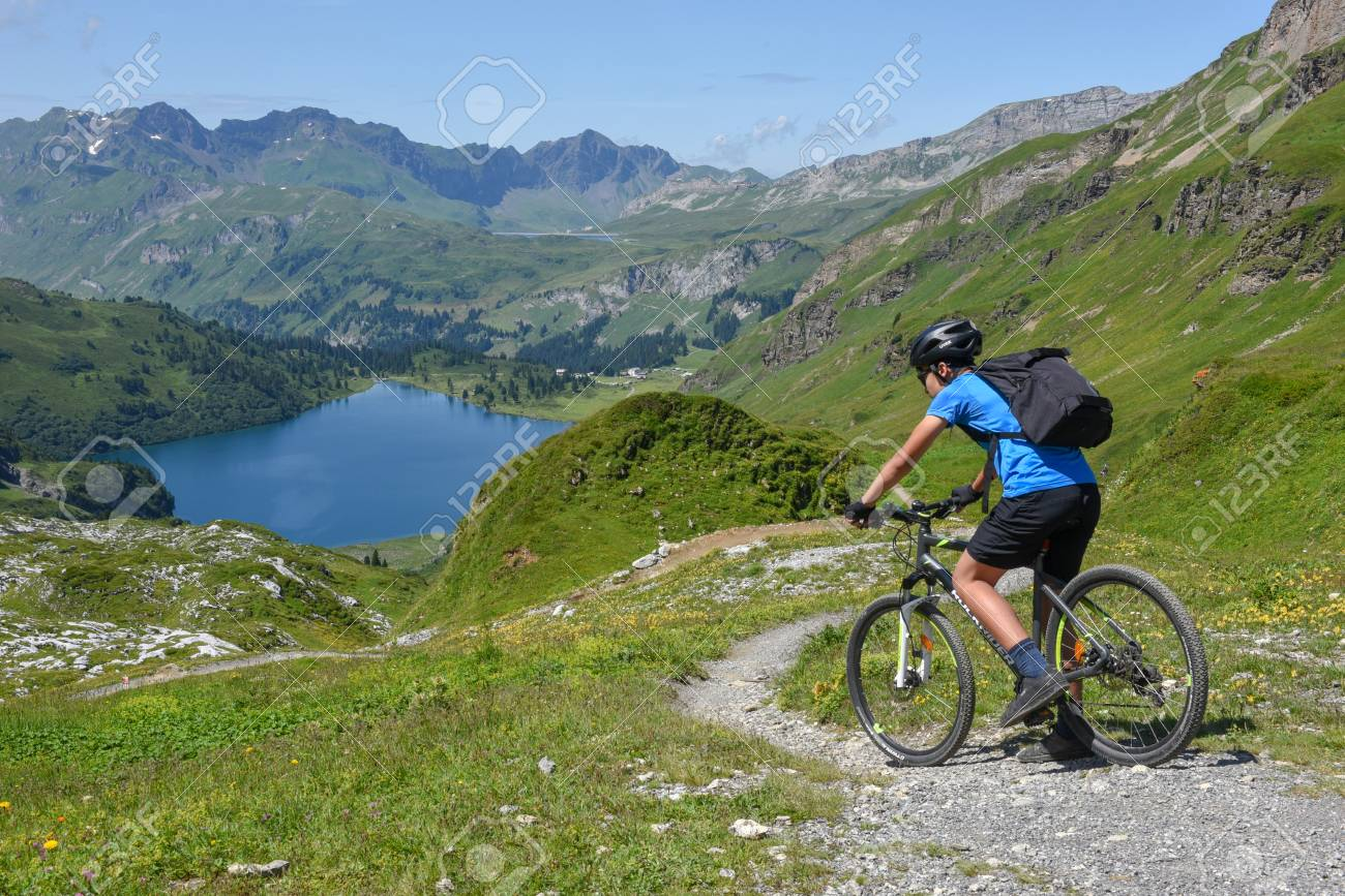 Jochpass, Switzerland - 4 august 2018: man on his mountain bike going down the path from Jochpass over Engelberg in the Swiss Alps - 131402862