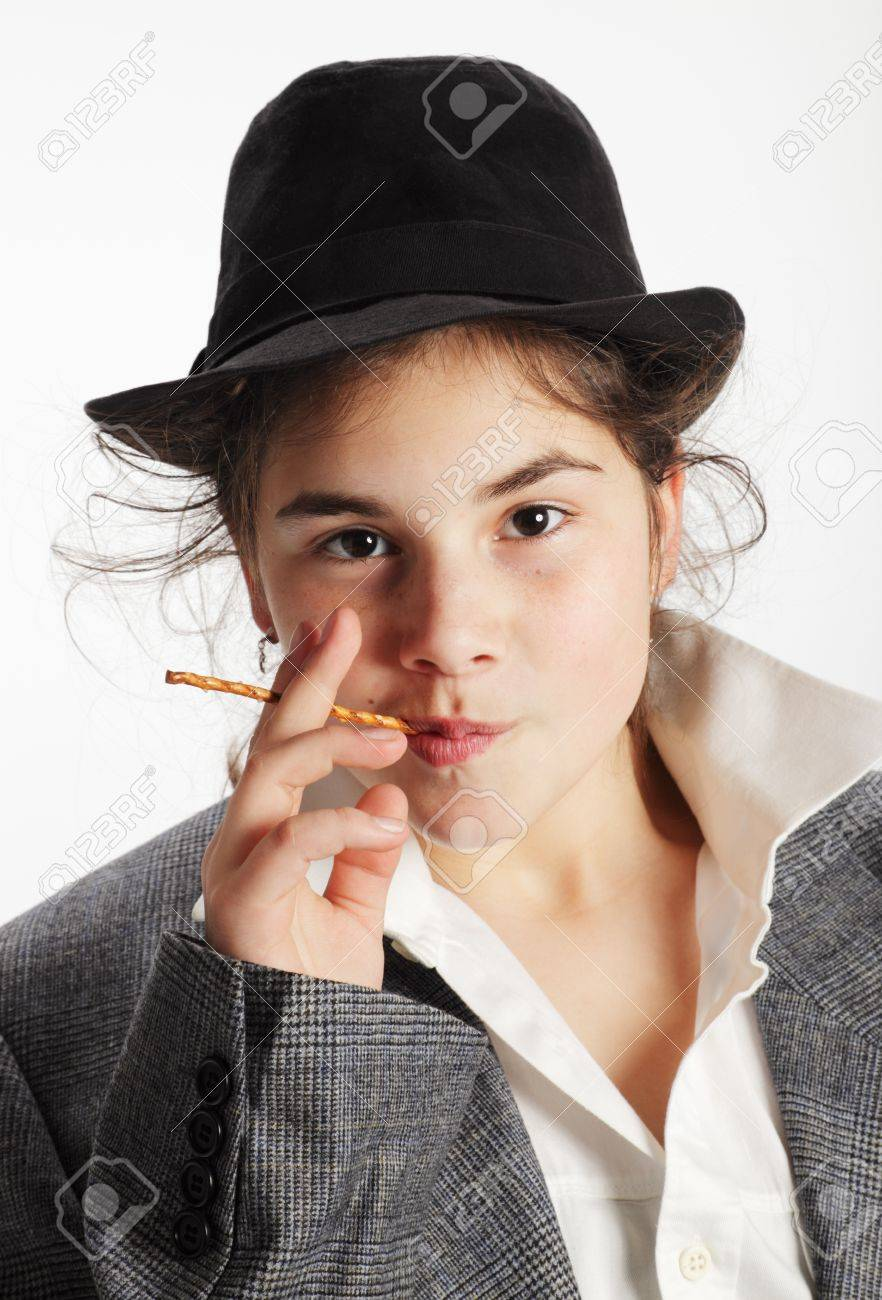 Teenage girl with black hat and suit, holding a pretzel stick to her mouth. Stock Photo - 10088063
