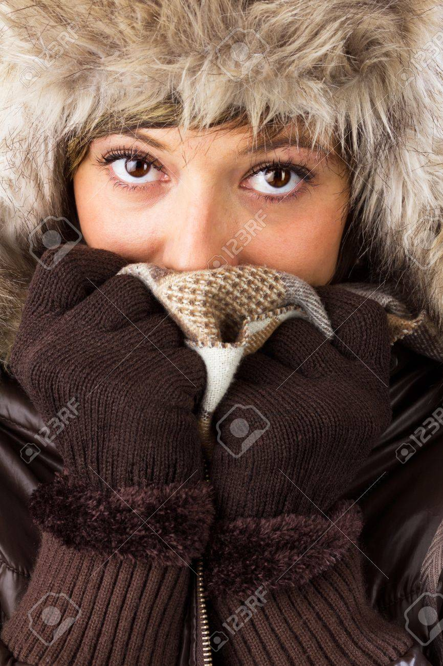 Beautiful young woman with big bright eyes in winter clothes covers her face to protect from the cold  Studio shot as a wintry close up portrait Stock Photo - 16470316