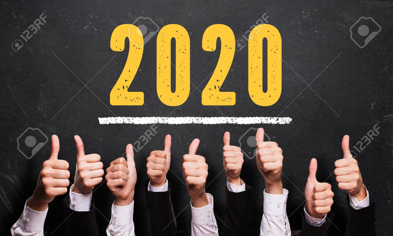 many thumbs up in front of blackboard with message 2020 - 133767904