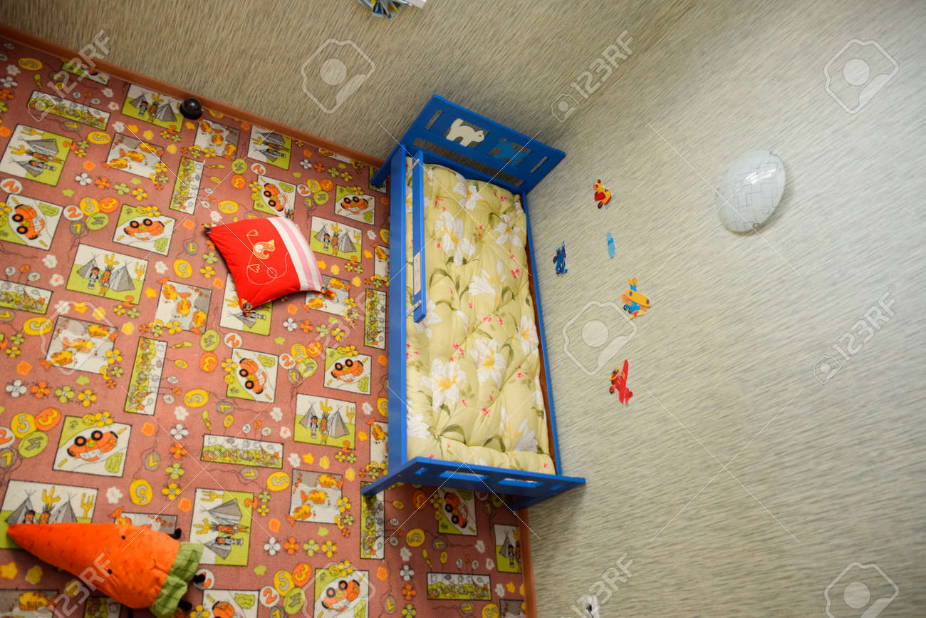 Novorossiysk, Russia - May 20, 2018: Childrens room, top view. Toys on the floor and a crib in the corner. - 133522191