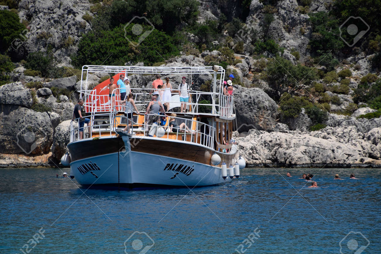 Demre, Turkey - May 21, 2019: Tourists swim in the sea near a pleasure yacht. The Mediterranean Sea off the coast of Kekova and Demre. Many vacationers are swimming in the Mediterranean Sea near the cruise boat. - 133522566