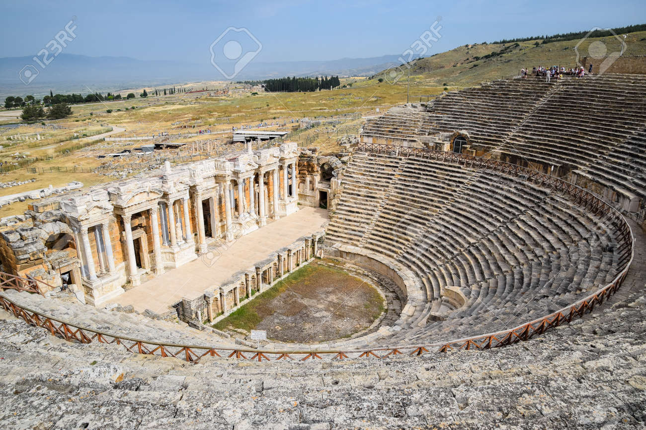 Pamukkale, Hierapolis, Turkey - May 22, 2019: Ancient antique amphitheater in the city of Hierapolis in Turkey. Steps and antique statues with columns in the amphitheater - 133523214