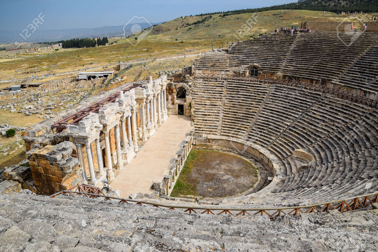 Pamukkale, Hierapolis, Turkey - May 22, 2019: Ancient antique amphitheater in the city of Hierapolis in Turkey. Steps and antique statues with columns in the amphitheater - 133523220