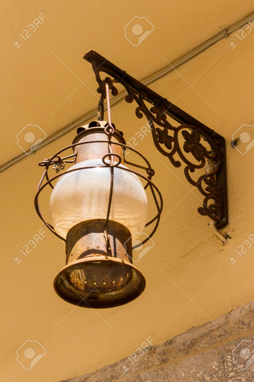 Close Up Of Old Glass Metal Oil Mediterranean Lantern On Old House In Small  Romantic Village