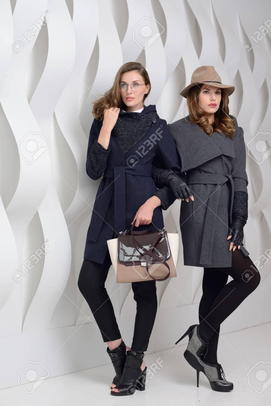 0e7904ed3 Young Girls In Studio Posing In Coats Stock Photo