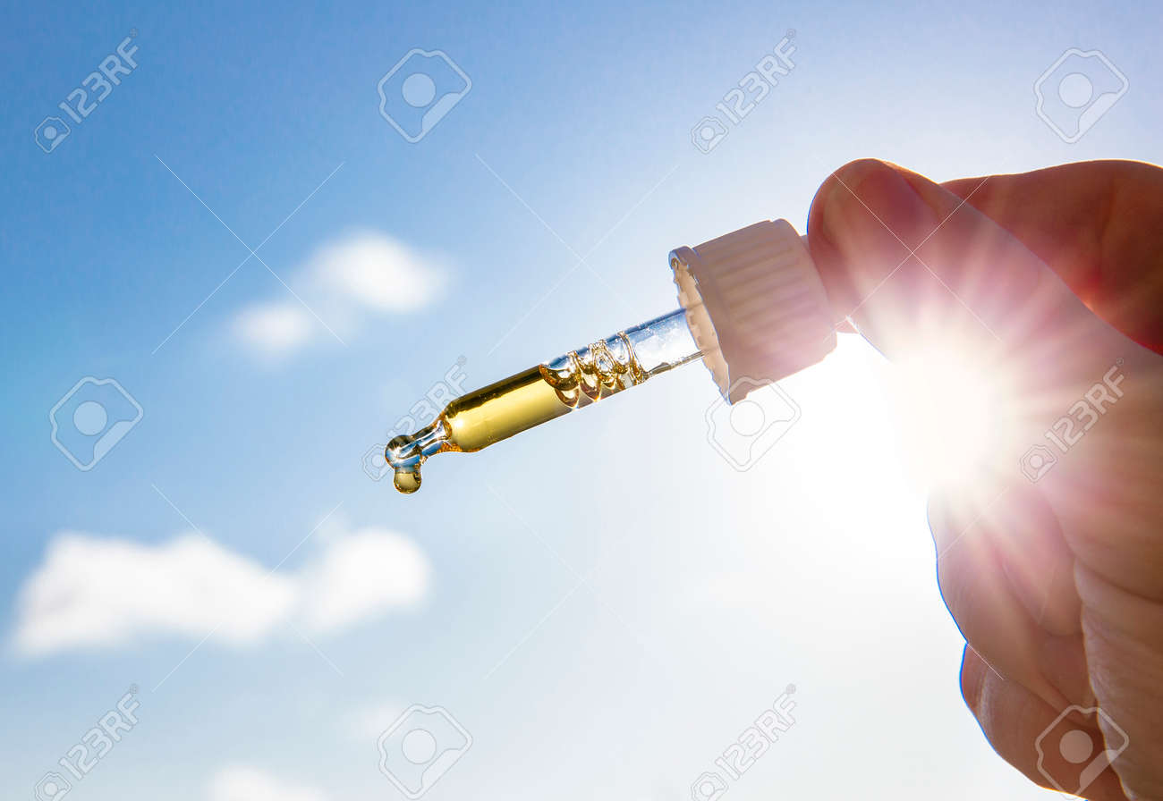 Hand holding dropper pipette with nice golden liquid D-vitamin against sun and blue sky on sunny day. Vitamin D keeps you healthy while lack of sun in winter, cure concept. - 158178057
