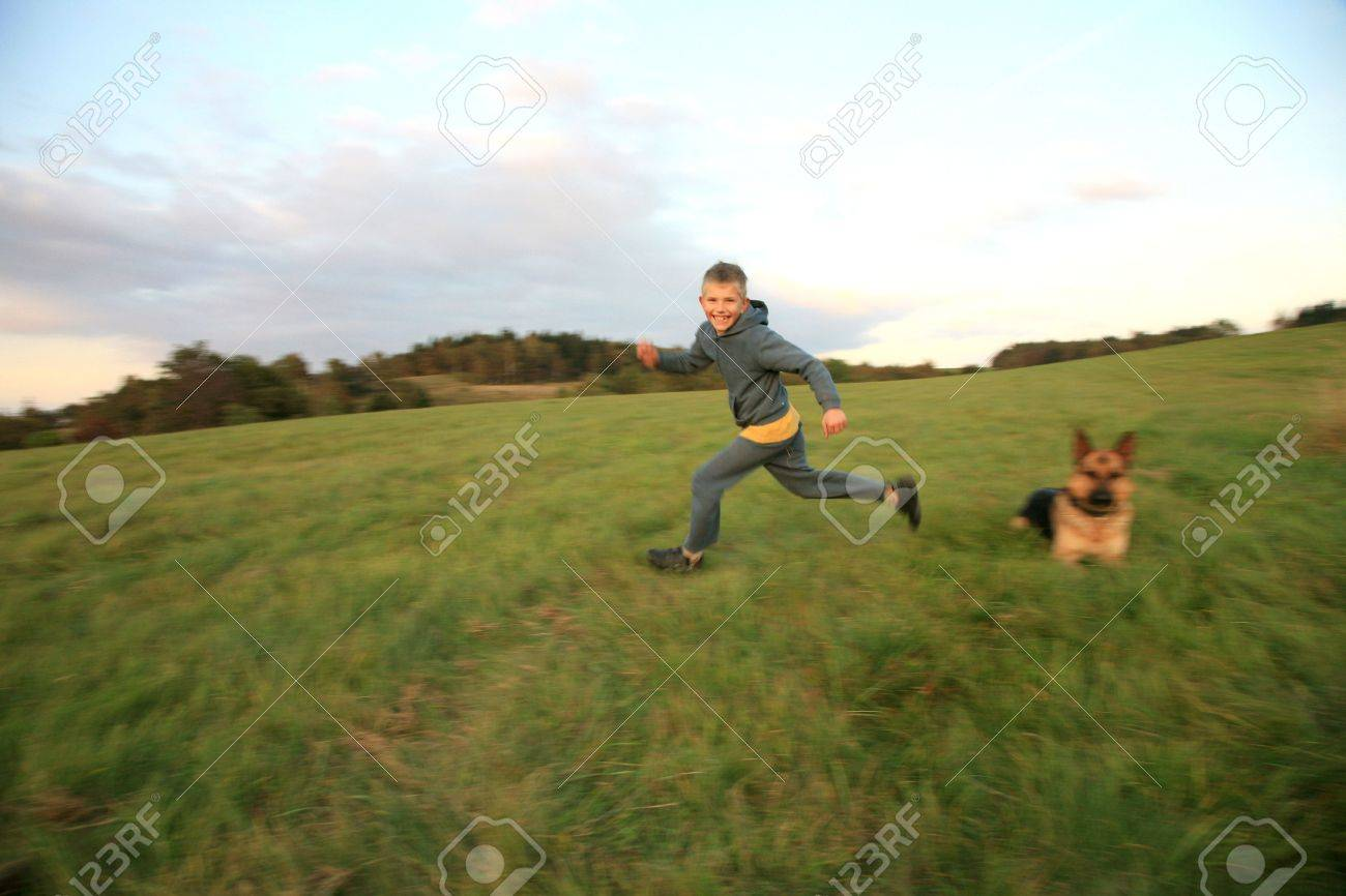Happy, little boy running on the green, mountain meadow at sunset with his faithful a large dog - German Shepherd. Stock Photo - 5617061