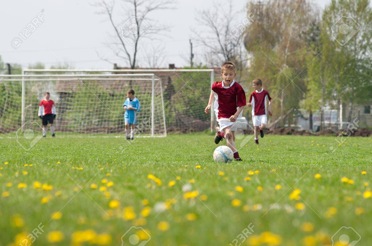 Little Boy  playing soccer on the sports field Stock Photo - 9647145