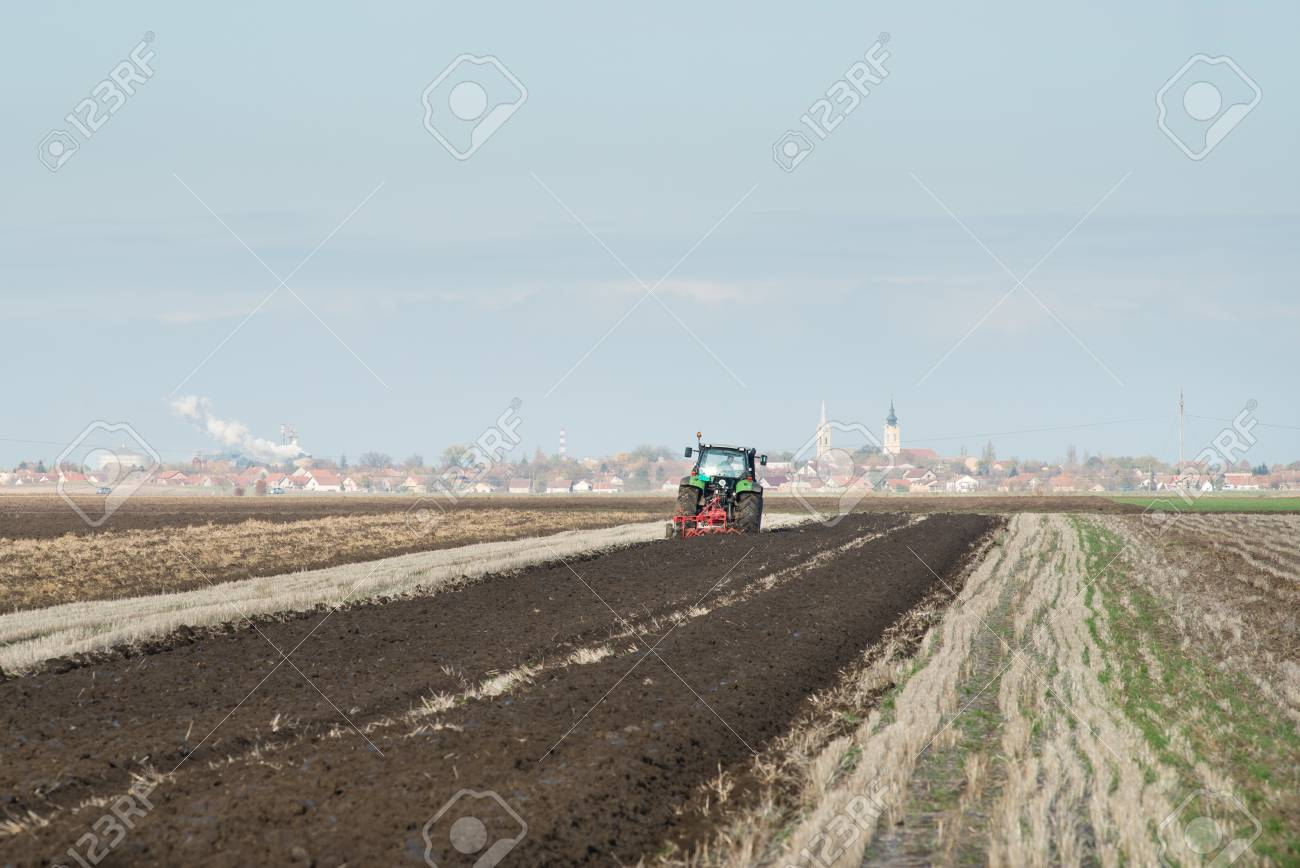 green Tractor Plowing in Autumn Stock Photo - 16335954