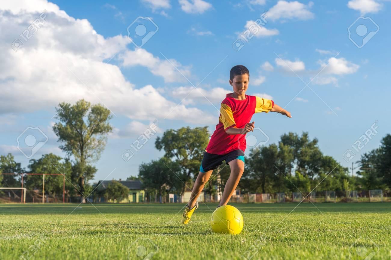 Little Boy Kicking ball at Goal - 42852313