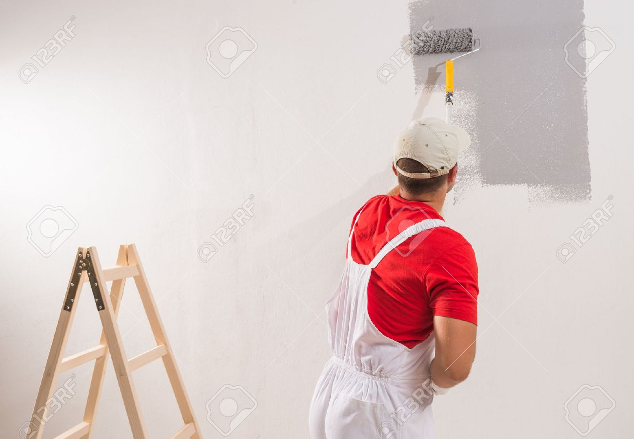 Person painting wall - Stock Photo Young Man On Painting Wall With Roller