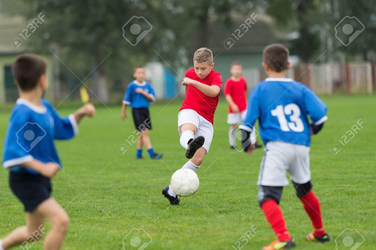 boy kicking football on the sports field - 46794914