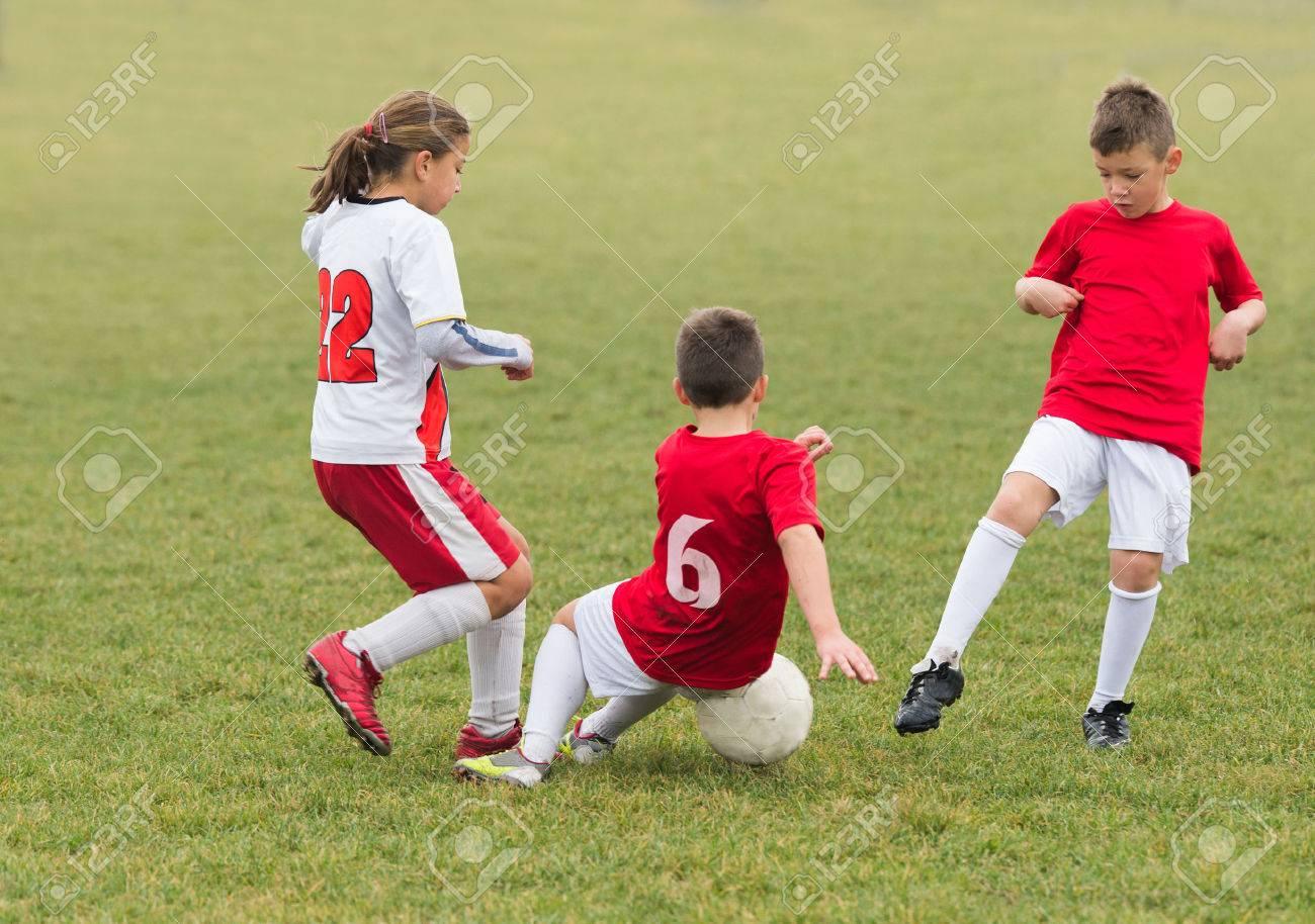 kids kicking football on the sports field - 48541290