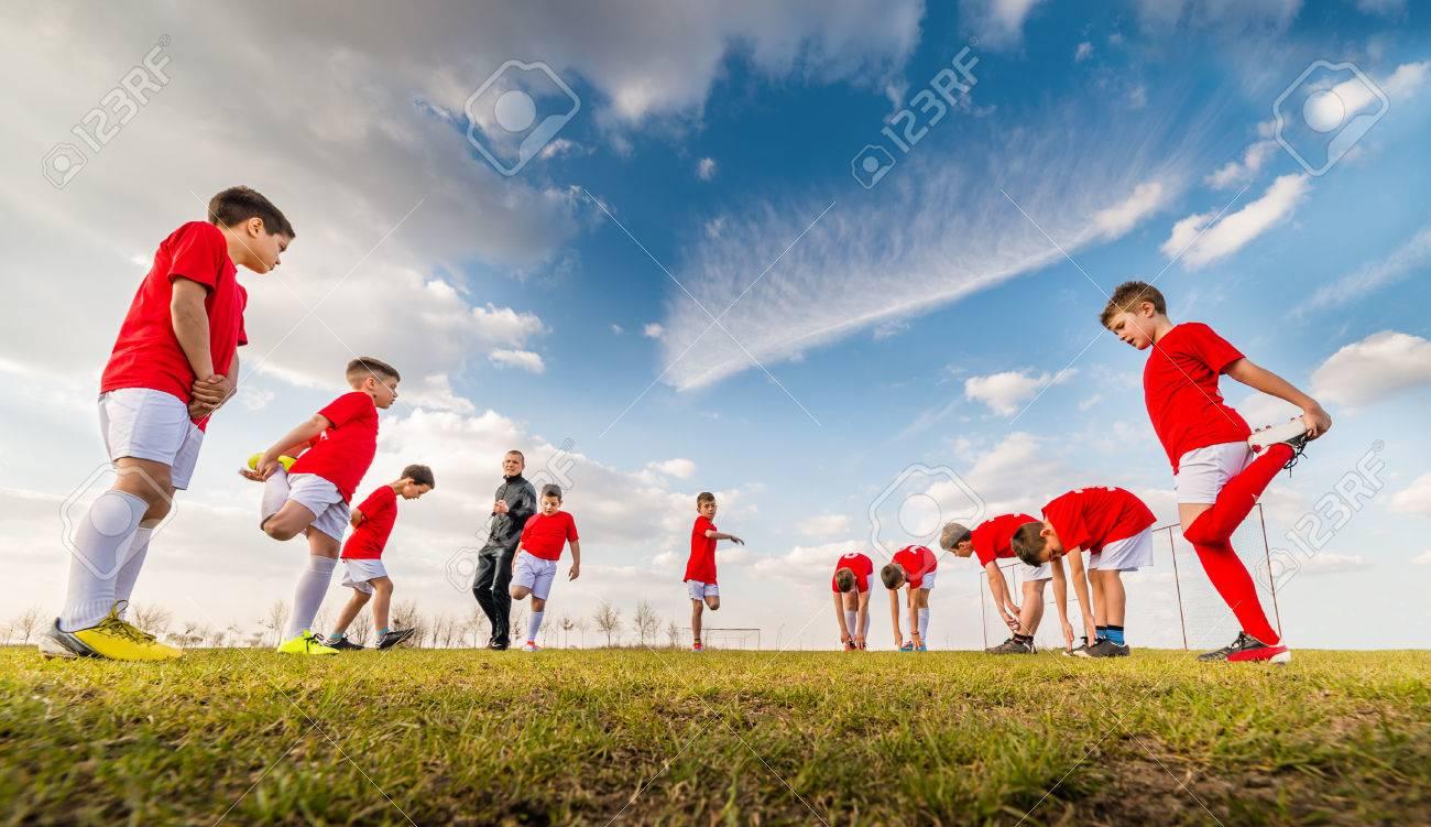 Kids soccer team exercise on soccer field - 56207471