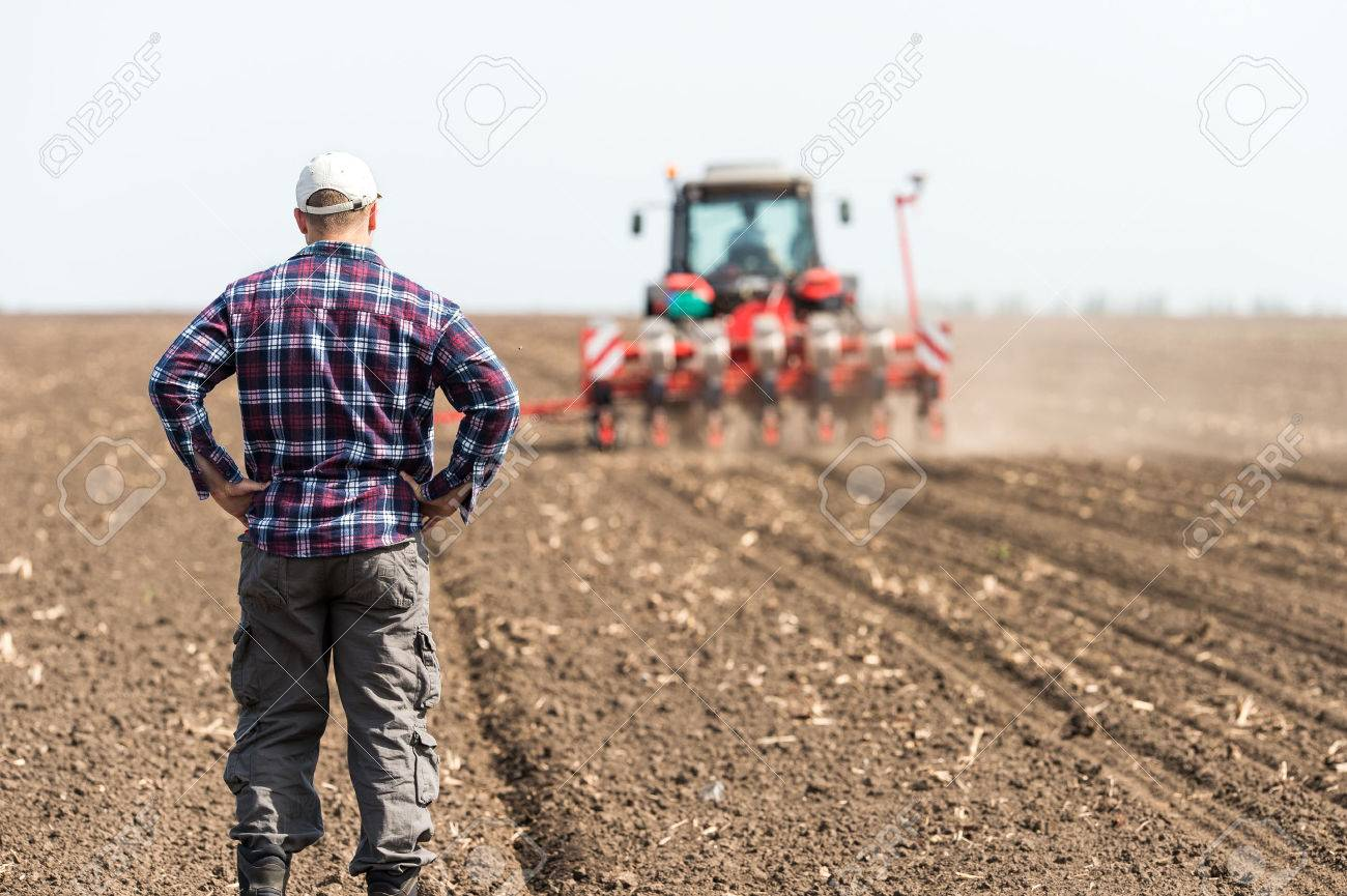 young farmer on farmland with tractor in background - 57048344