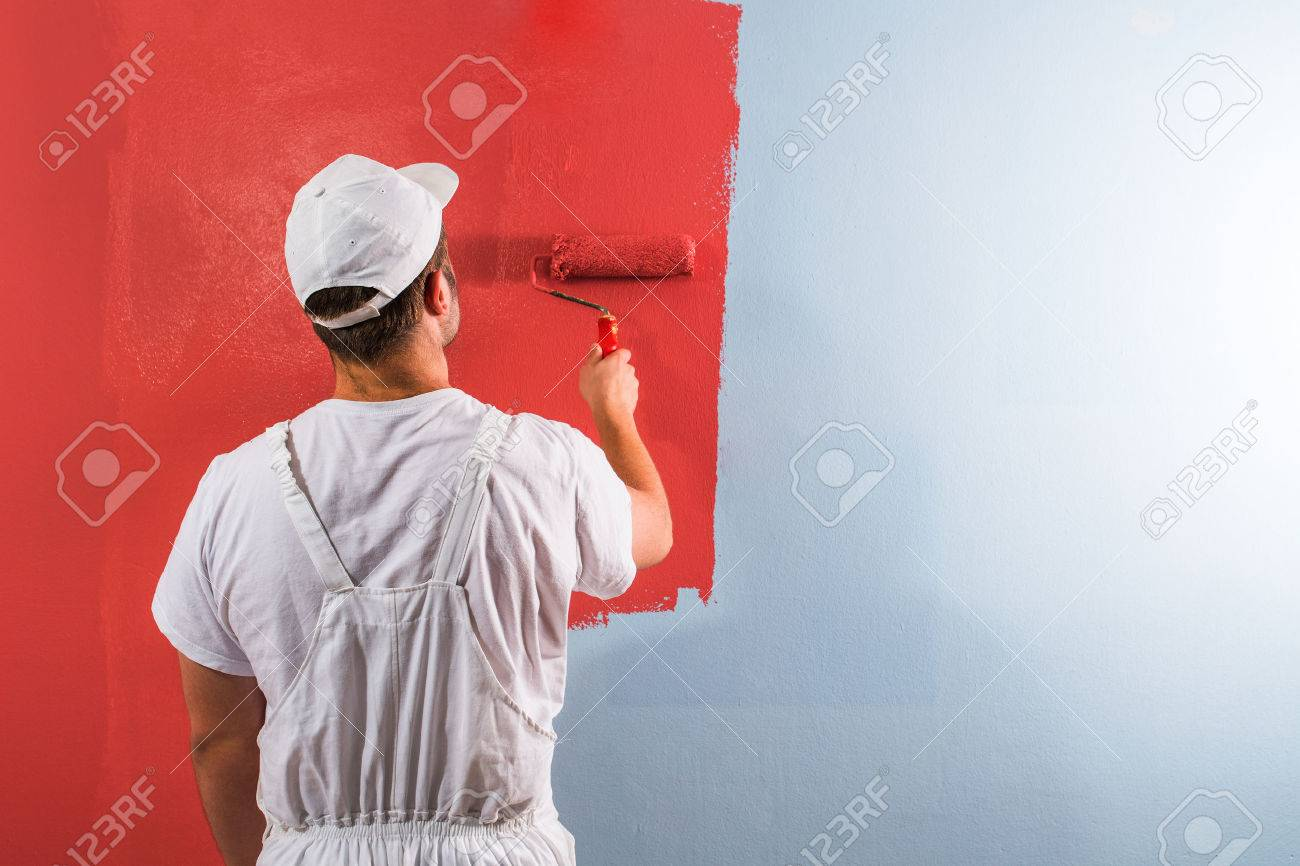 Young man painting wall with roller - 65723415