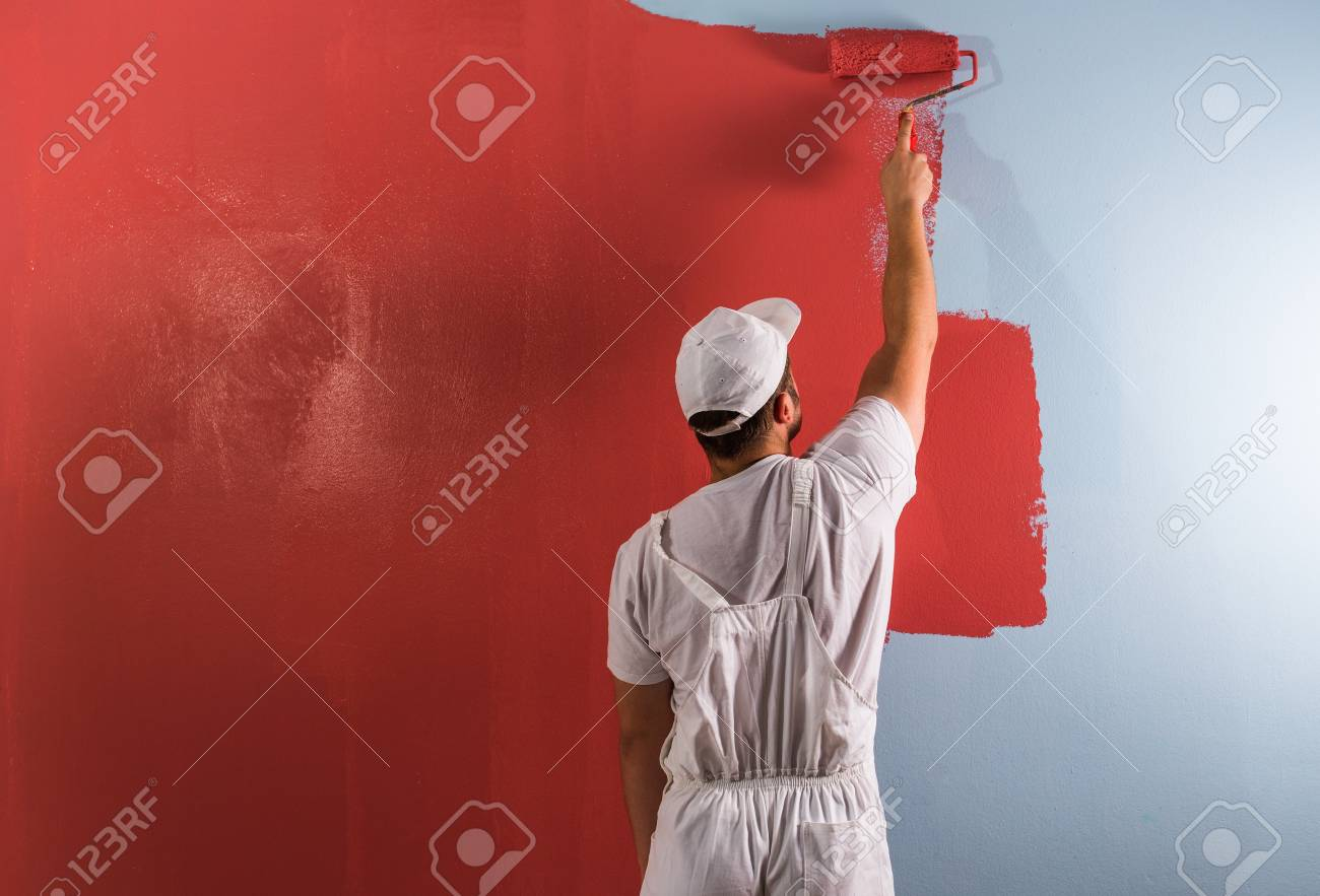 Young man painting wall with roller - 65457448