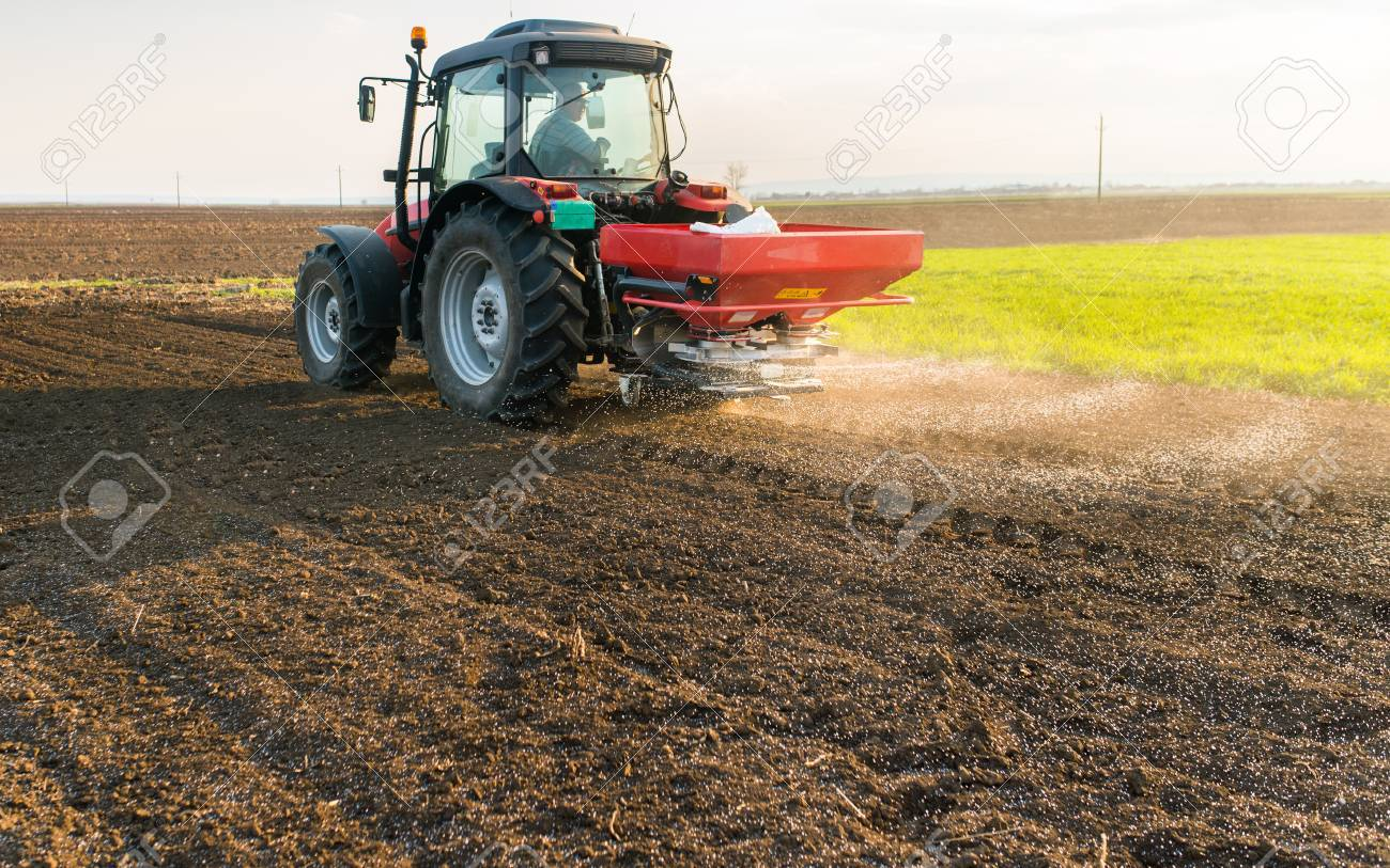 Tractor spreading artificial fertilizers in field - 74572652