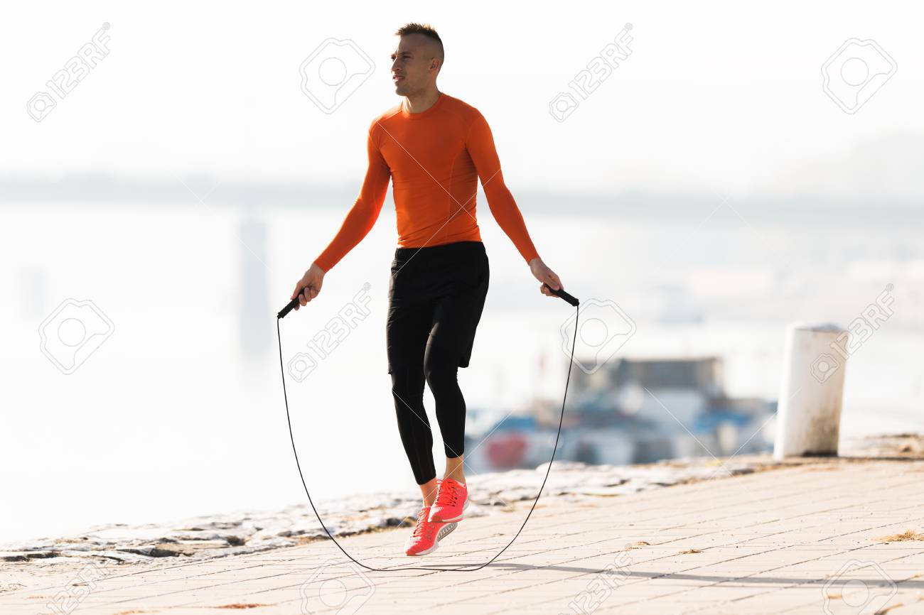Handsome young man wearing sportswear and skipping rope at quay during autumn - 91171869