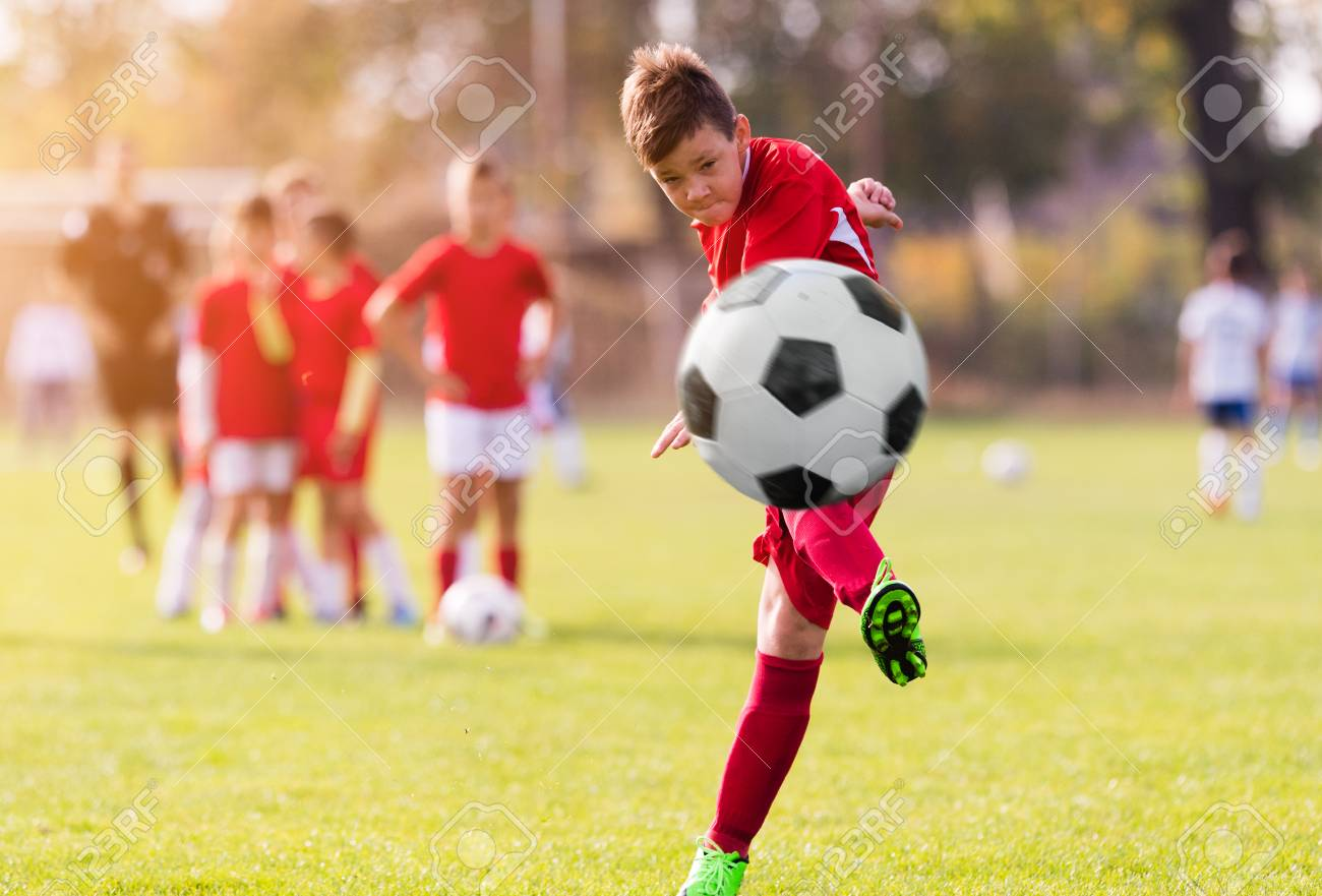Boy kicking football on the sports field during soccer match - 96141834