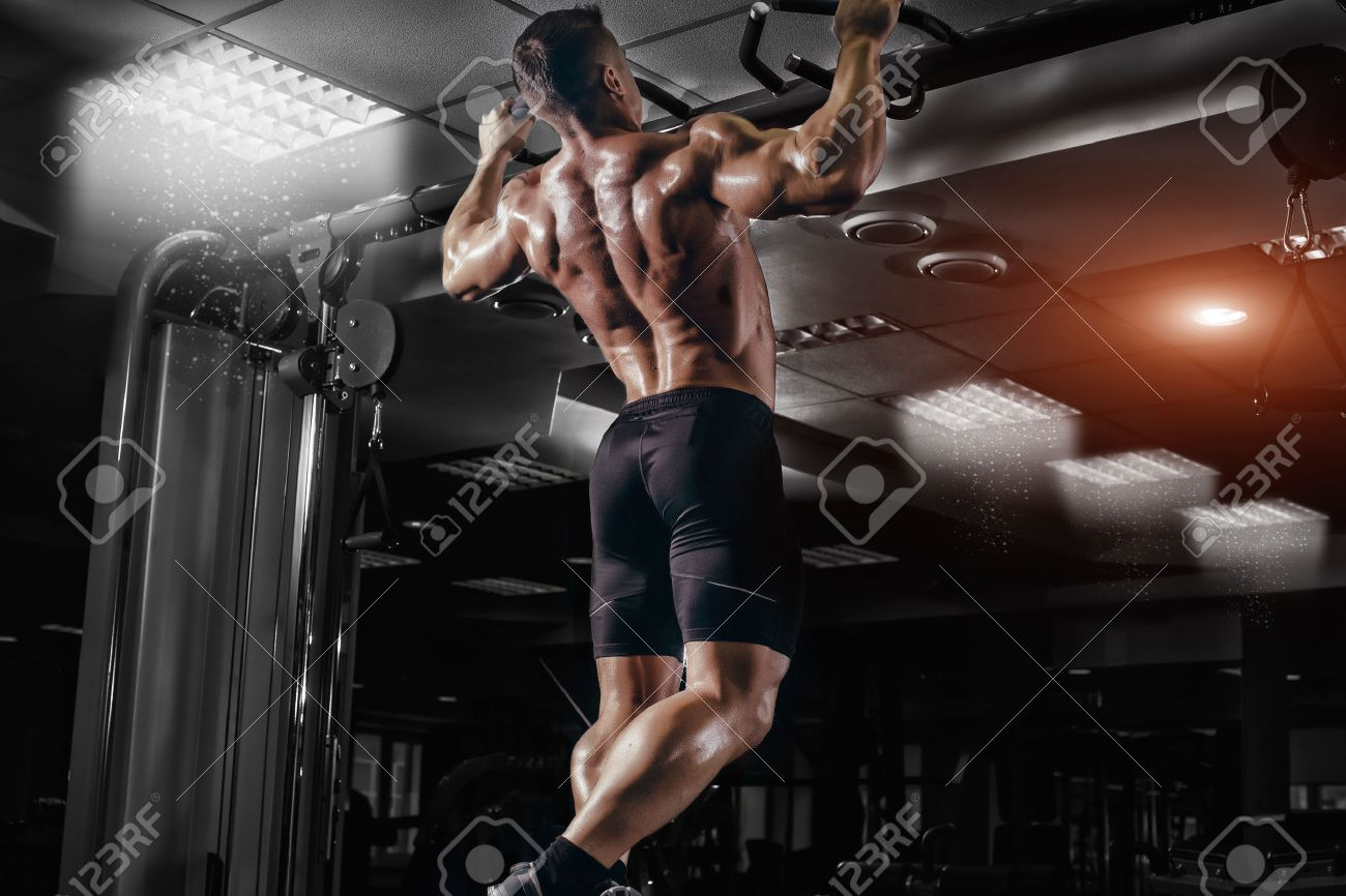 Muscle athlete man in gym making elevations. Bodybuilder training in gym - 50925816