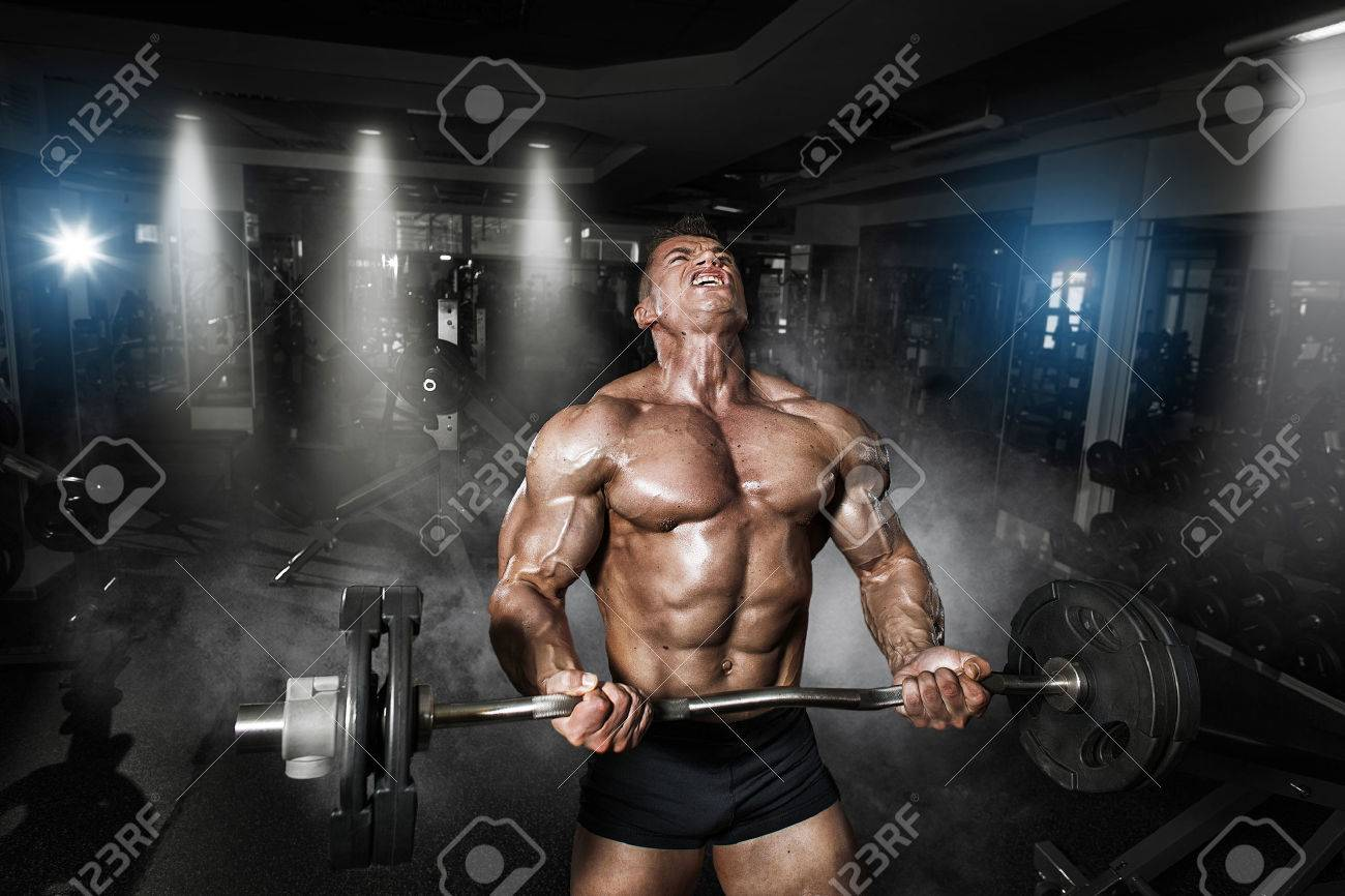 Athlete muscular bodybuilder in the gym training with bar - 50925225