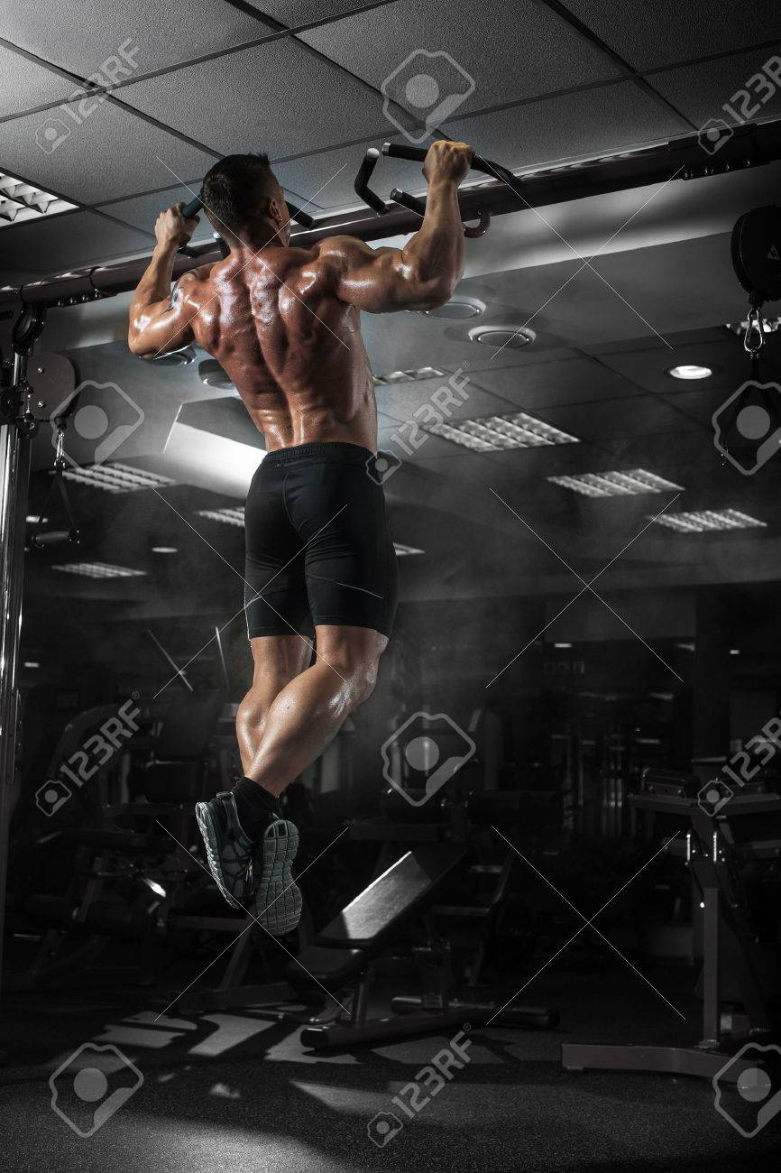 Muscle athlete man in gym making elevations. Bodybuilder training in gym - 50925372