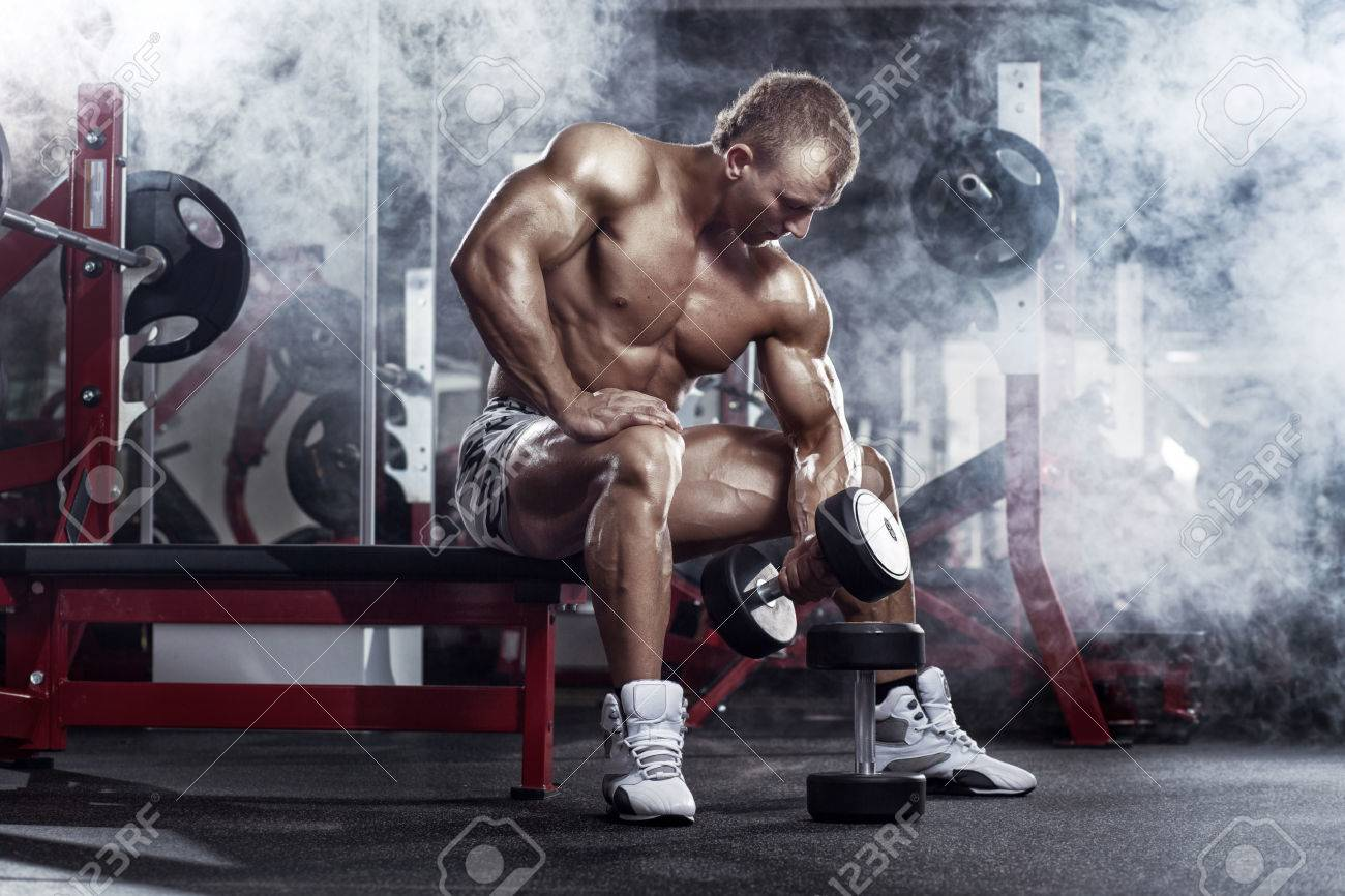 very power athletic guy , execute exercise press with dumbbells, workout in sport hall - 51672851