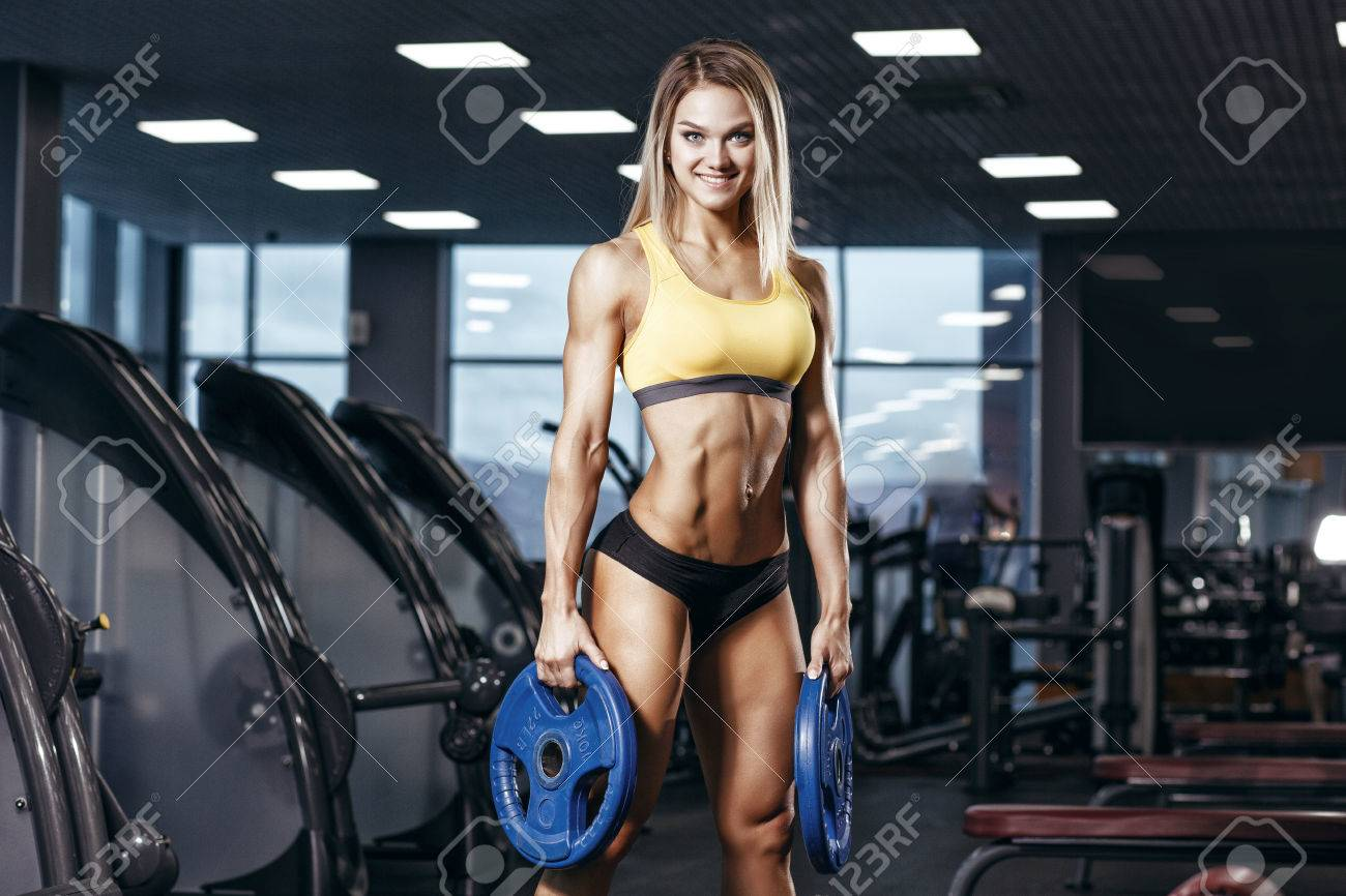 abfe6a7b95263 Sexy athletic sport smiling girl with perfect fitness body doing workout  hard training with weights in