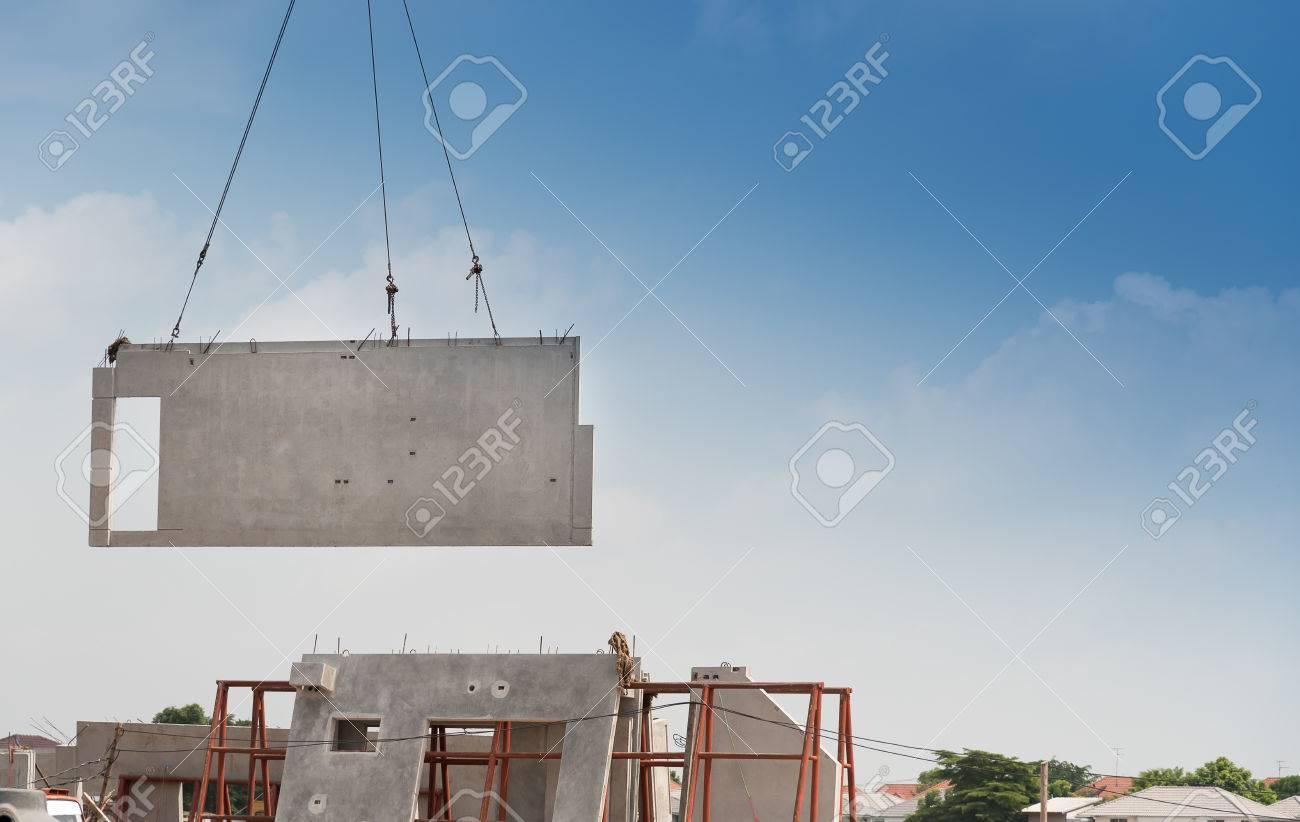 Construction site crane is lifting a precast concrete wall panel