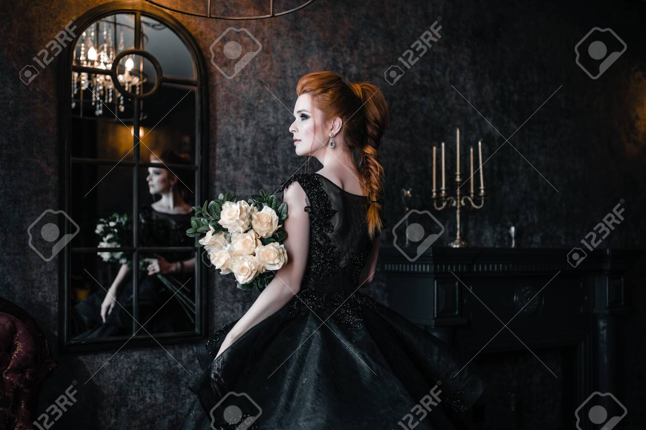 Attractive woman in black dress in medieval interior - 131765268
