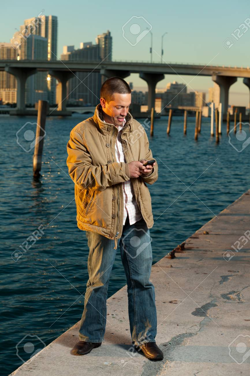 Handsome Hispanic Man on a Mobile Phone with downtown skyline Stock Photo - 8540788