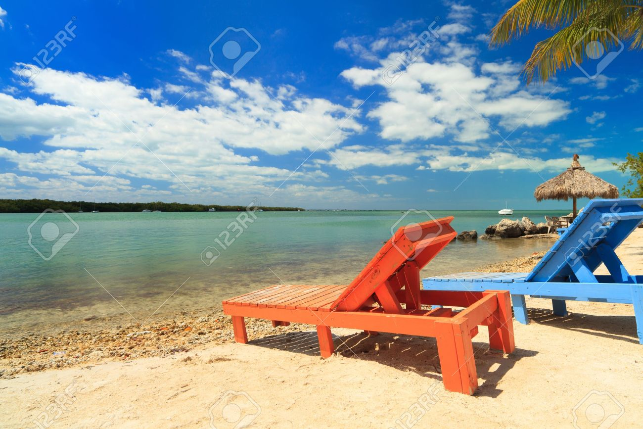 Wooden beach lounge chair - Stock Photo Wooden Beach Lounge Chairs Along The Shoreline Of The Florida Keys With Pretty Blue Sky And Clouds And Thatched Hut In The Background