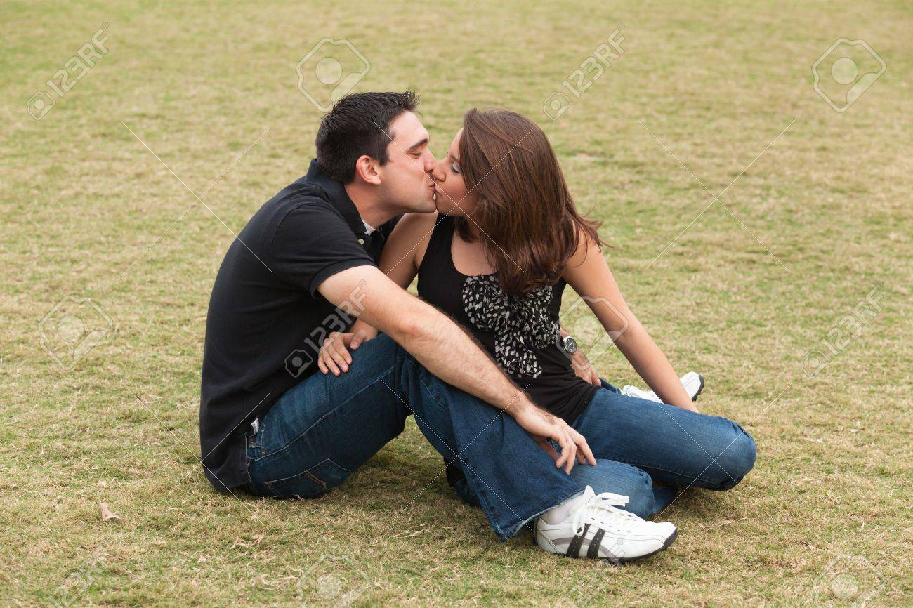 Young married couple  in a loving pose sitting on a lawn in a park Stock Photo - 14743240