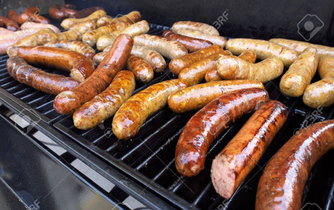 Fresh sausage and hot dogs grilling outdoors on a gas barbeque grill - 17742409